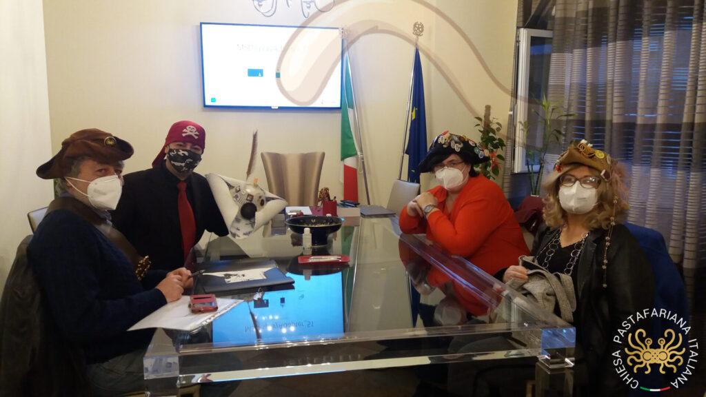 Quattro Pastafariani seduti intorno al tavolo dello studio notarile per fondare l'ente religioso Chiesa Pastafariana Italiana.